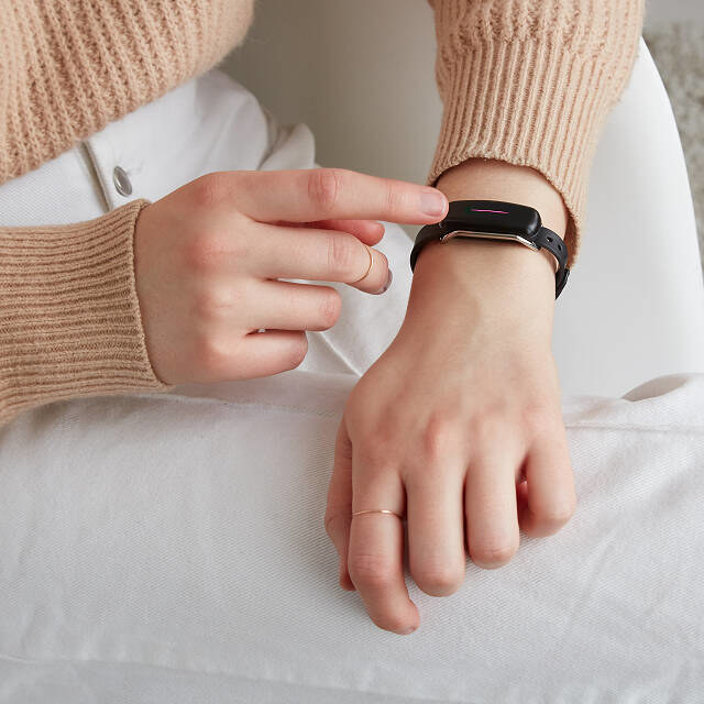 a model wearing the touch bracelet with a red light across the screen