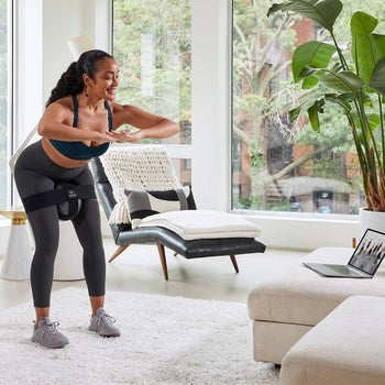 model using the equipment to workout in their living room