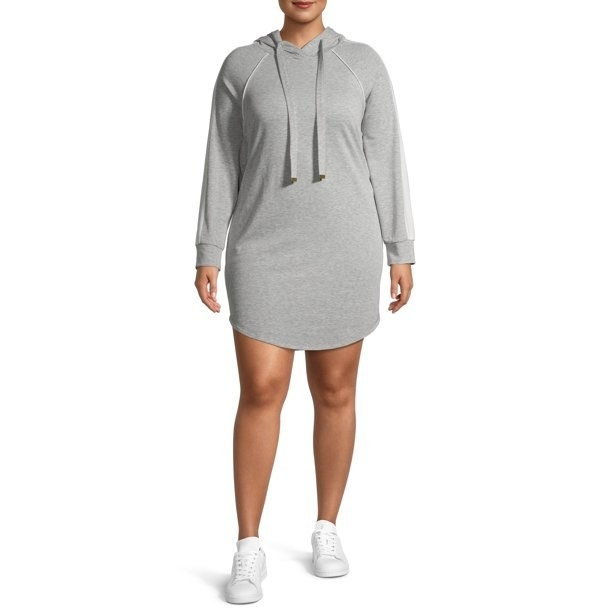 model wears gray sweatshirt dress with white sneakers