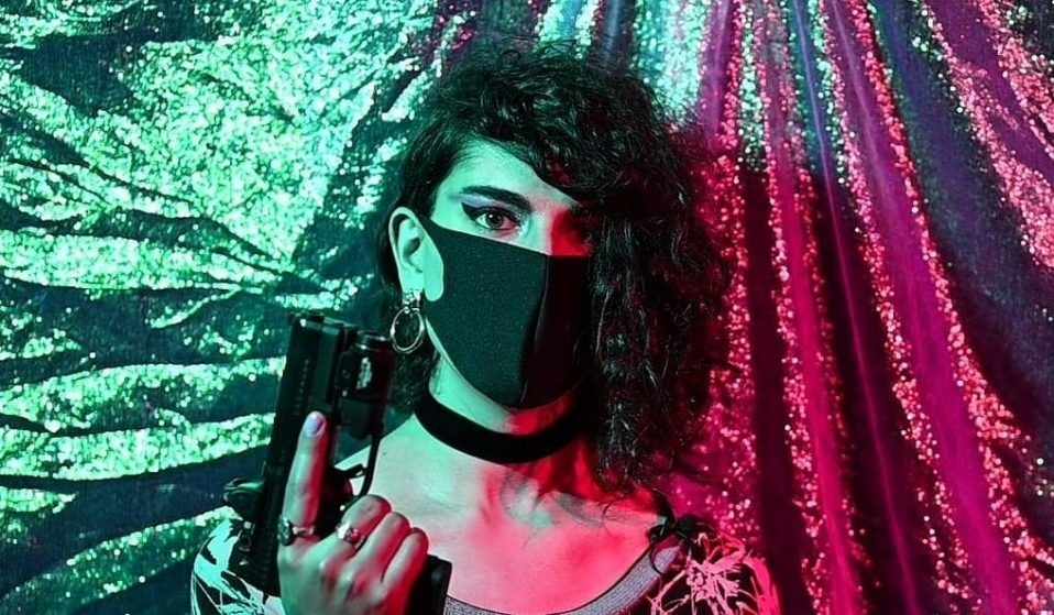 A person in a face mask holding a gun.