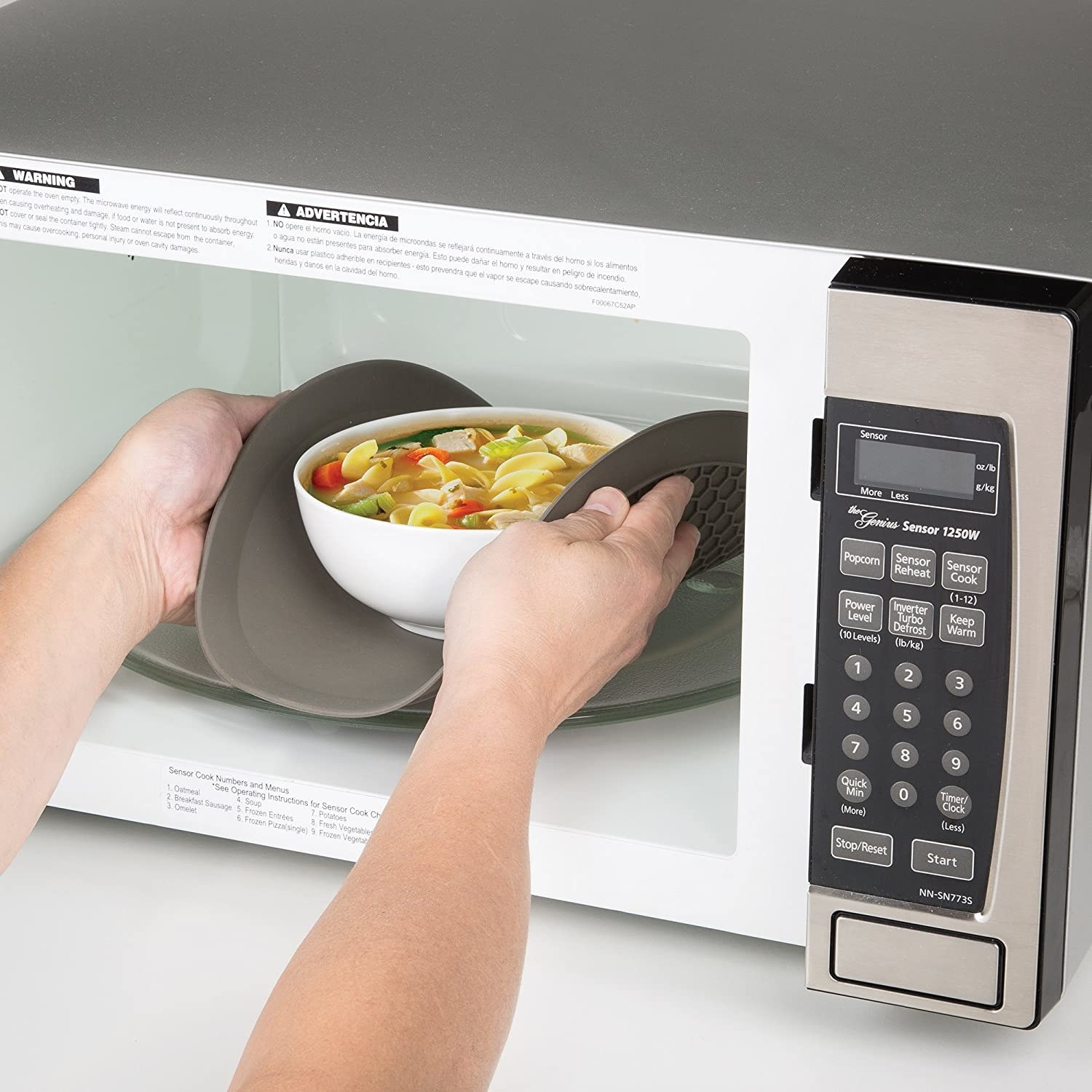 A person lifting a bowl of soup out of the microwave with the mat