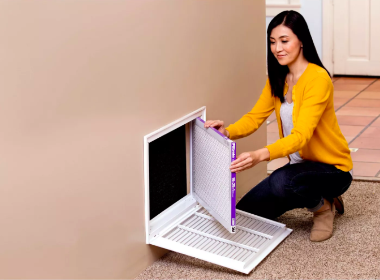 a person installing the replacement air filter into their HVAC system