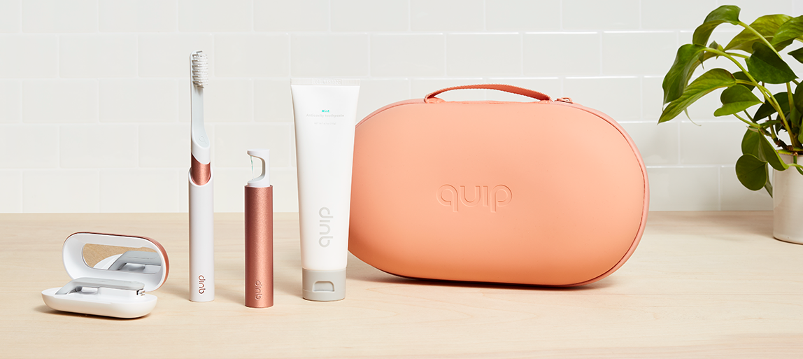 A quip toiletry case, floss holder, tube of toothpaste, and toothbrush