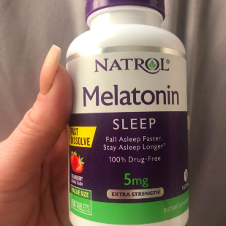 Reviewer holding up bottle of sleep tablets