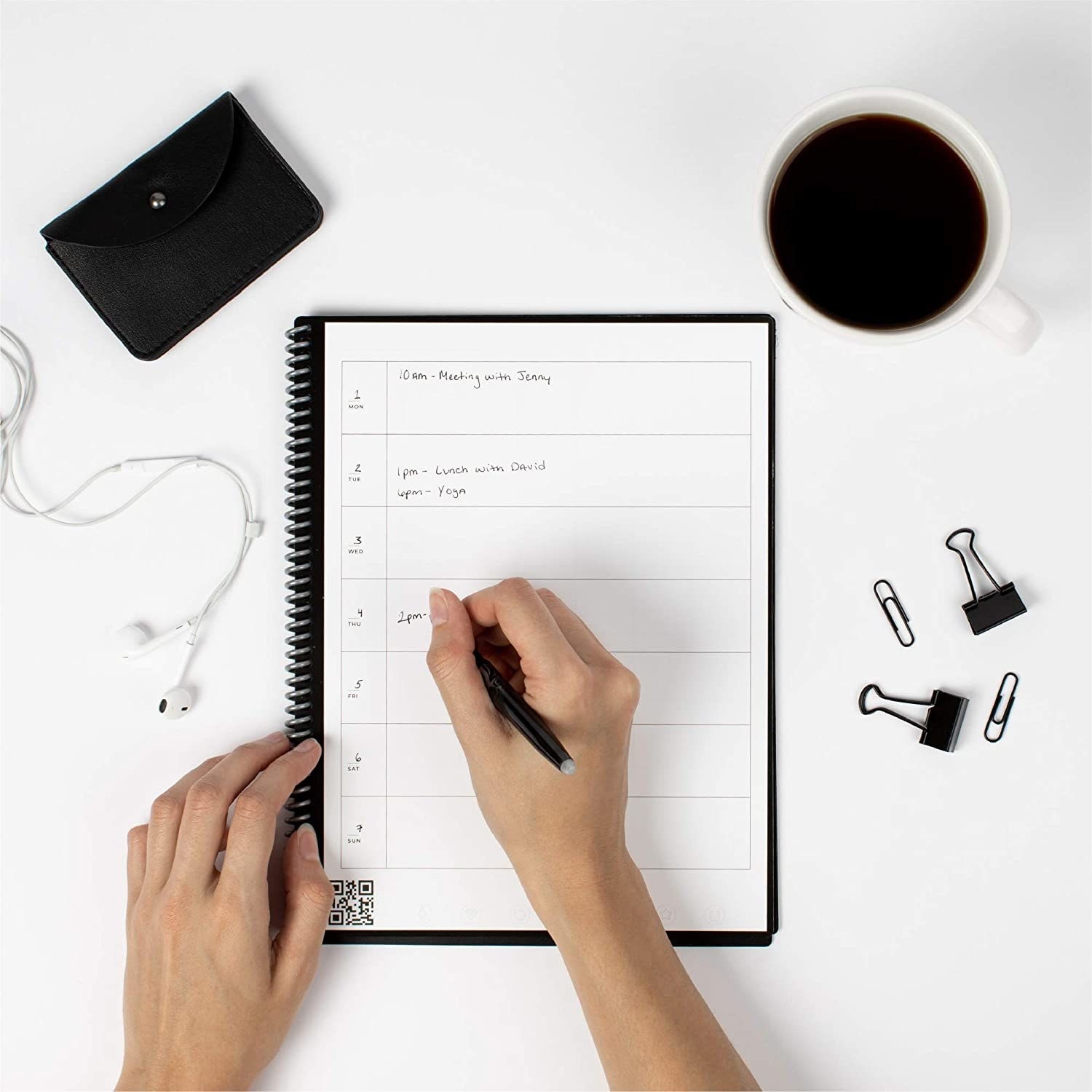 Model using pilot frixion pen to write in Rocketbook notebook on table