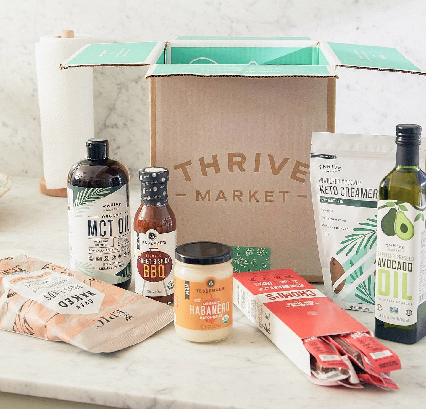 An open Thrive Market cardboard box surrounded by various grocery items like BBQ sauce,  jerkey sticks, and avocado oil