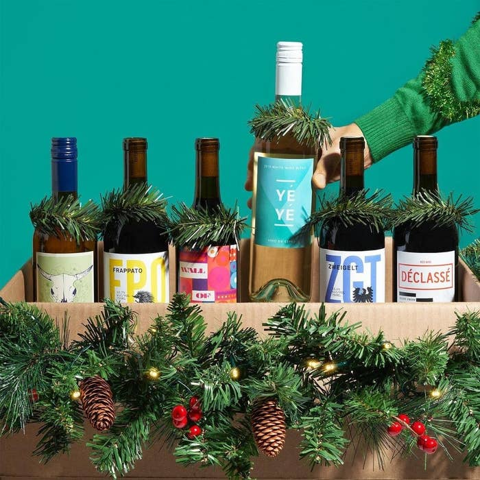 A hand putting a bottle of wine into a box filled with over bottles of wine decorated with tinsel and pine cones