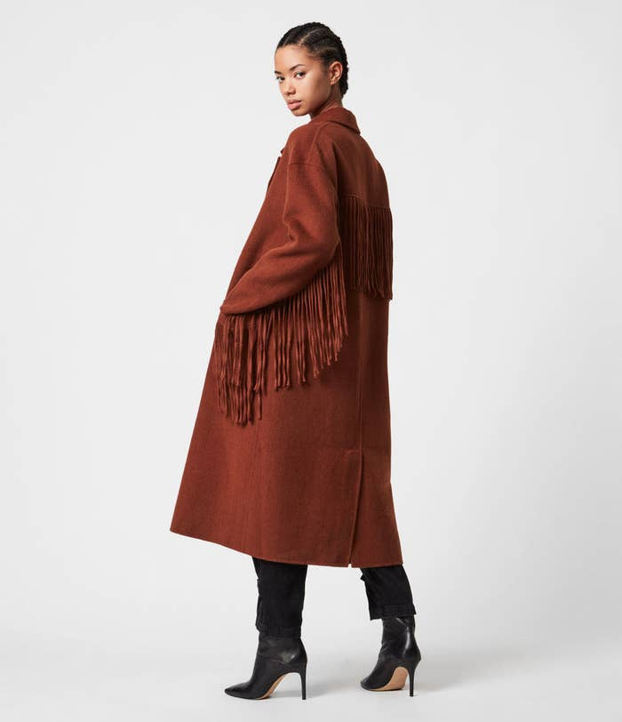 A model in the rust colored coat with fringe on the sleeves and back