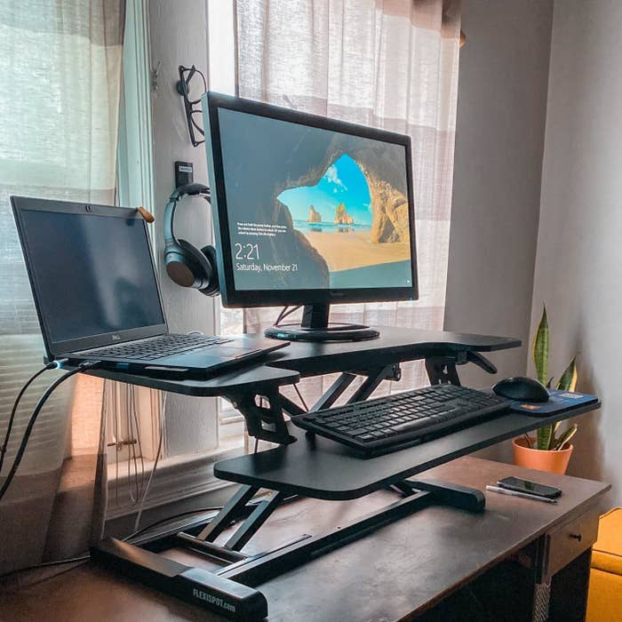 Reviewer standing desk converter in use on traditional desk