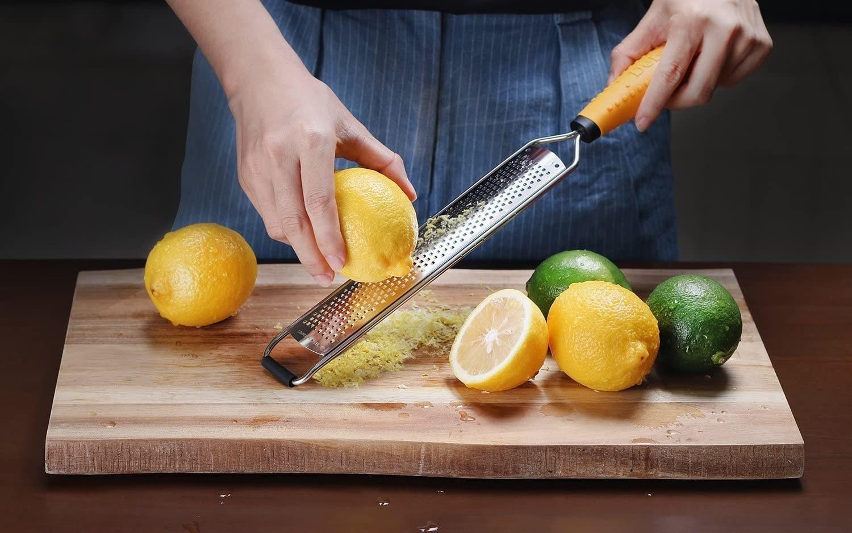 a model zesting a lemon over a cutting board