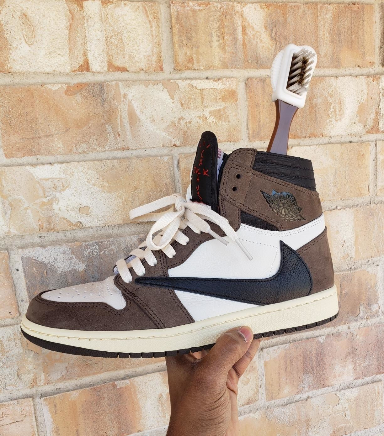 reviewer holing up their Travis Scott jordan 1 sneakers with the suede brush