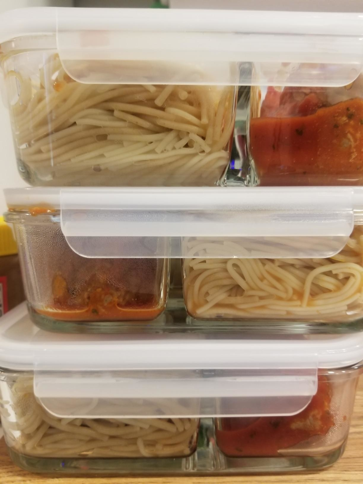 reviewer photo showing meal prep containers stacked in their fridge with pasta in them