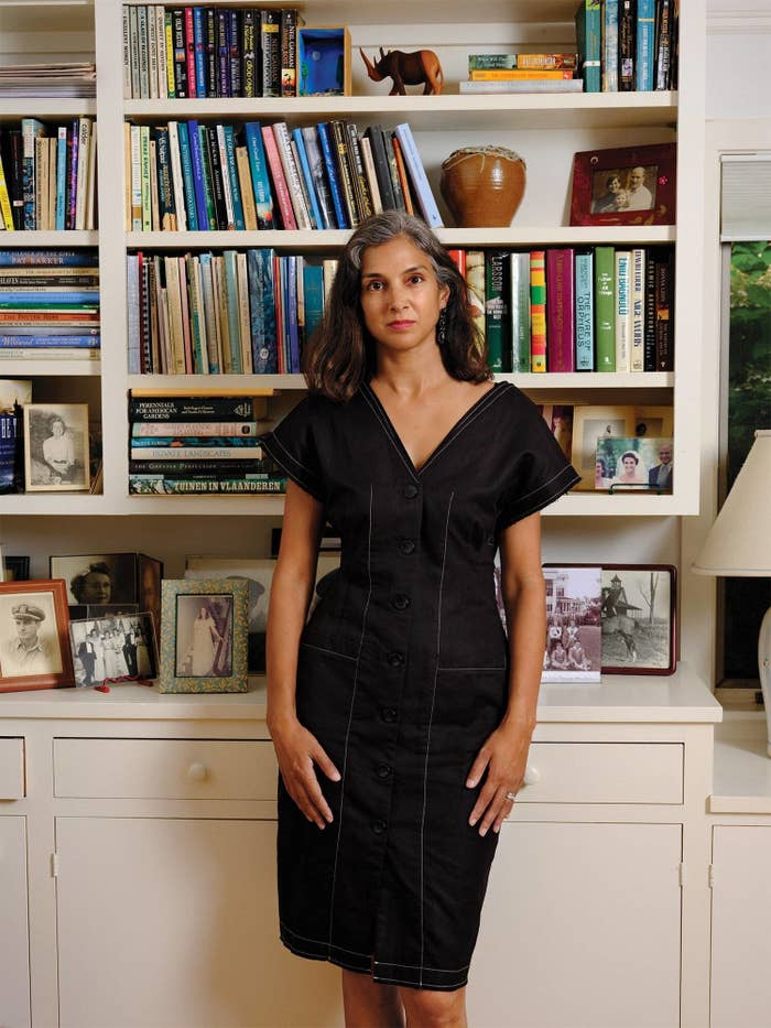 Radhika Jones stands in  front of a book shelf facing the camera