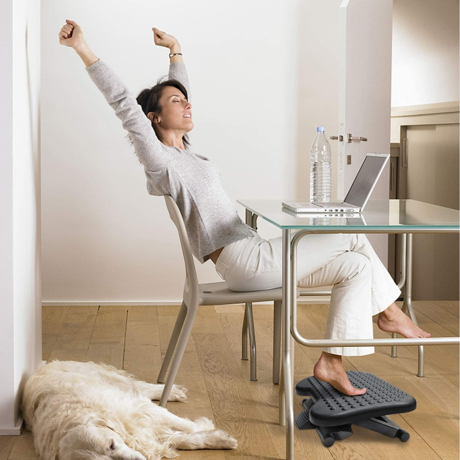 A person sitting on the desk with a small footrest underneath
