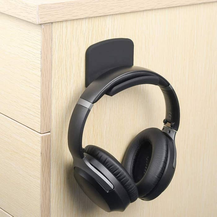 A pair of headphones hanging from a mount stuck to the side of a desk