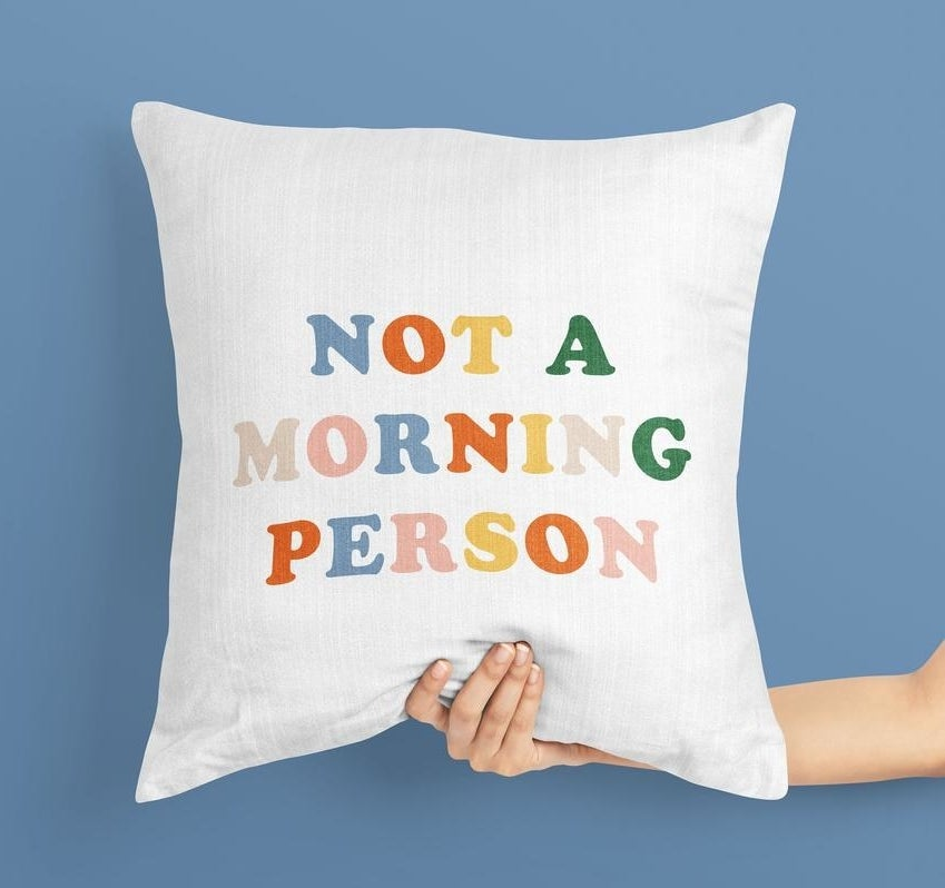 """model holding pillow that reads """"not a morning person"""""""