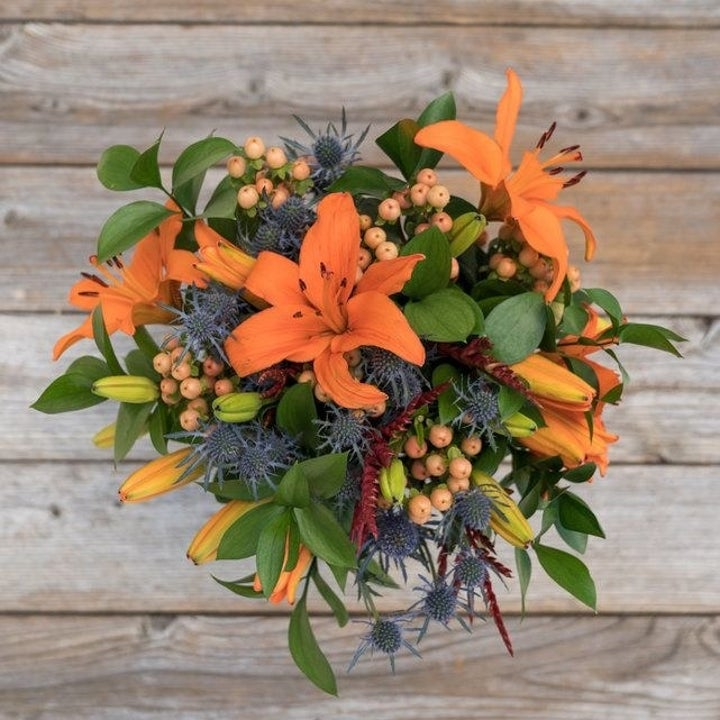 A top-down view of an orange and green bouquet of flowers