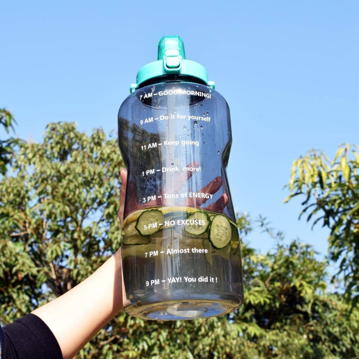 A person holding a large water bottle with sliced cucumbers inside