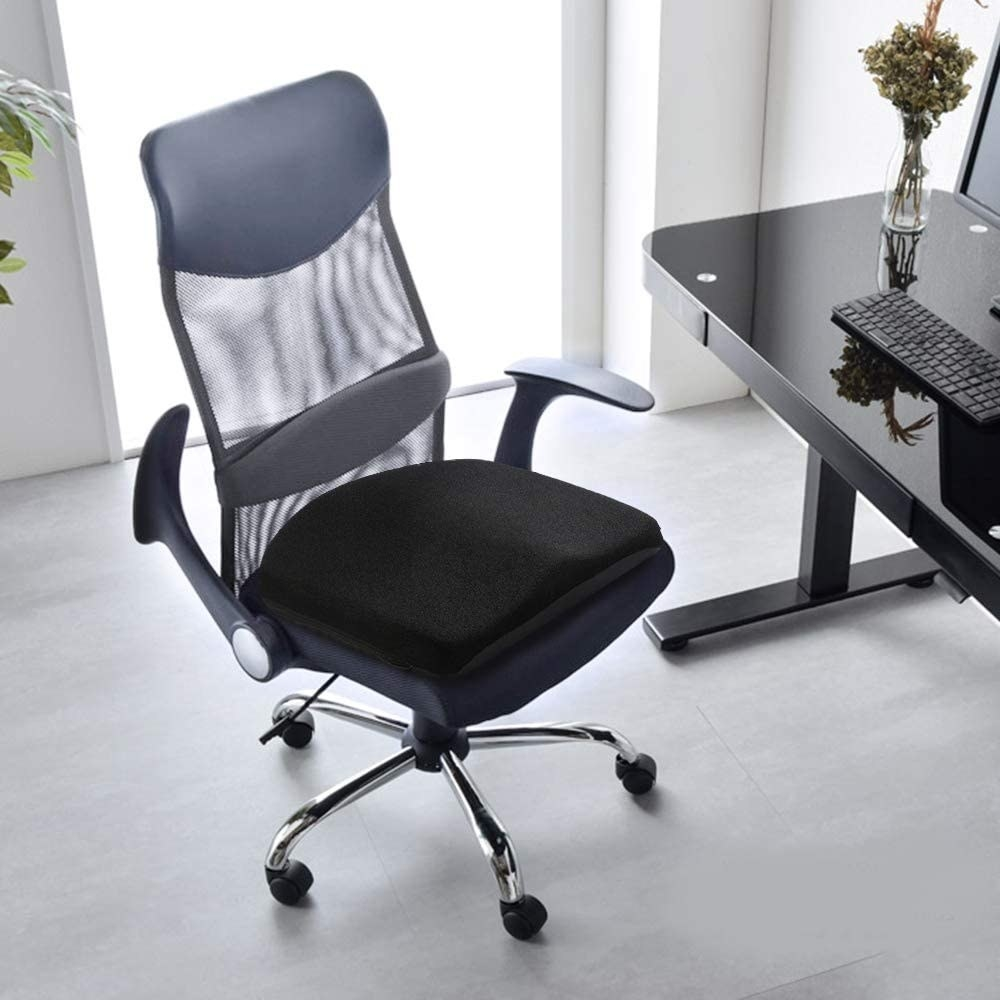 A comfy seat cushion on an swivel desk chair in front of a desk