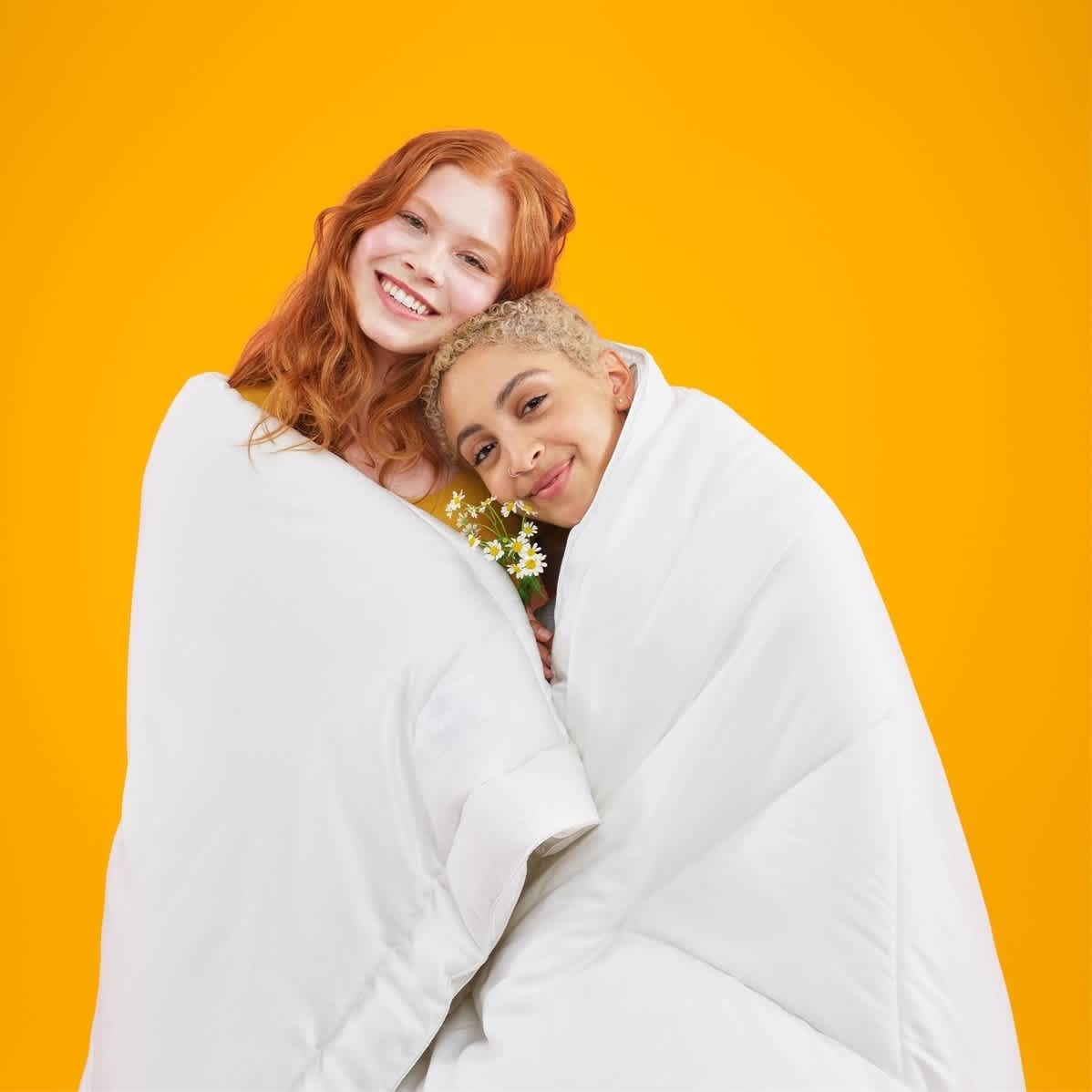 Two models wrapped up in the plush comforter