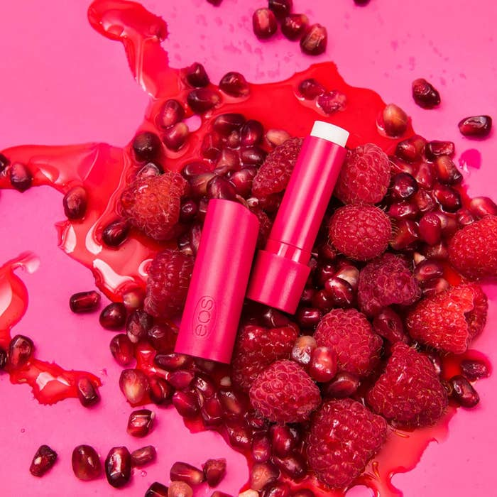 lip balm on a bed of strawberries and pomegranate seeds