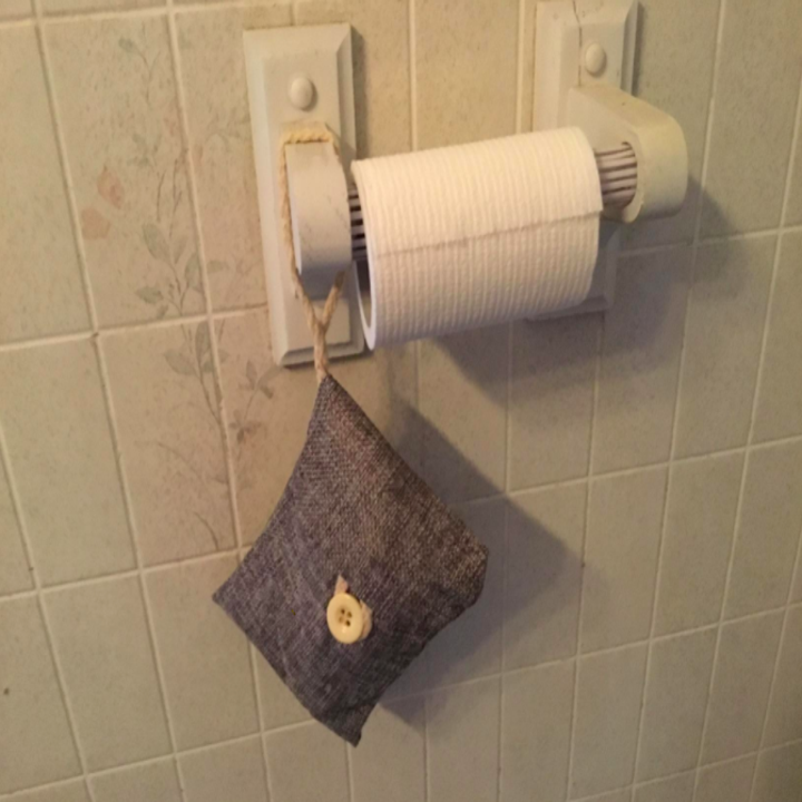a reviewer's photo of one of the bags hanging from a toilet paper holder