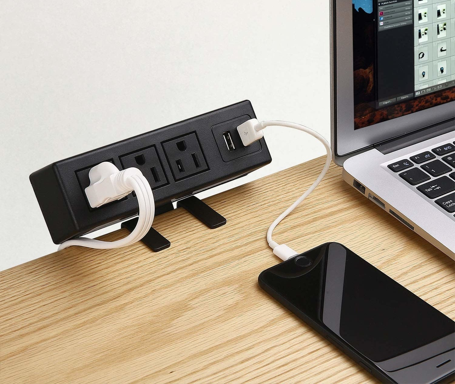 A small power bar clamped to the side of a desk with a cable and phone charger plugged in