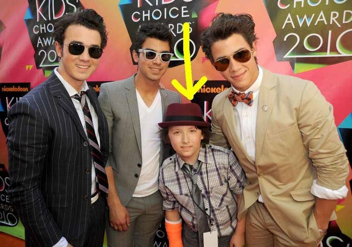 A photo of the Jonas Brothers plus Frankie, with an arrow pointing to Frankie, the much younger brother