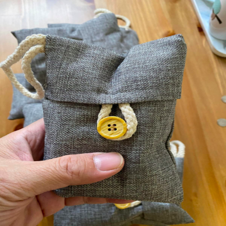 a different reviewer holding one of the charcoal bamboo bags