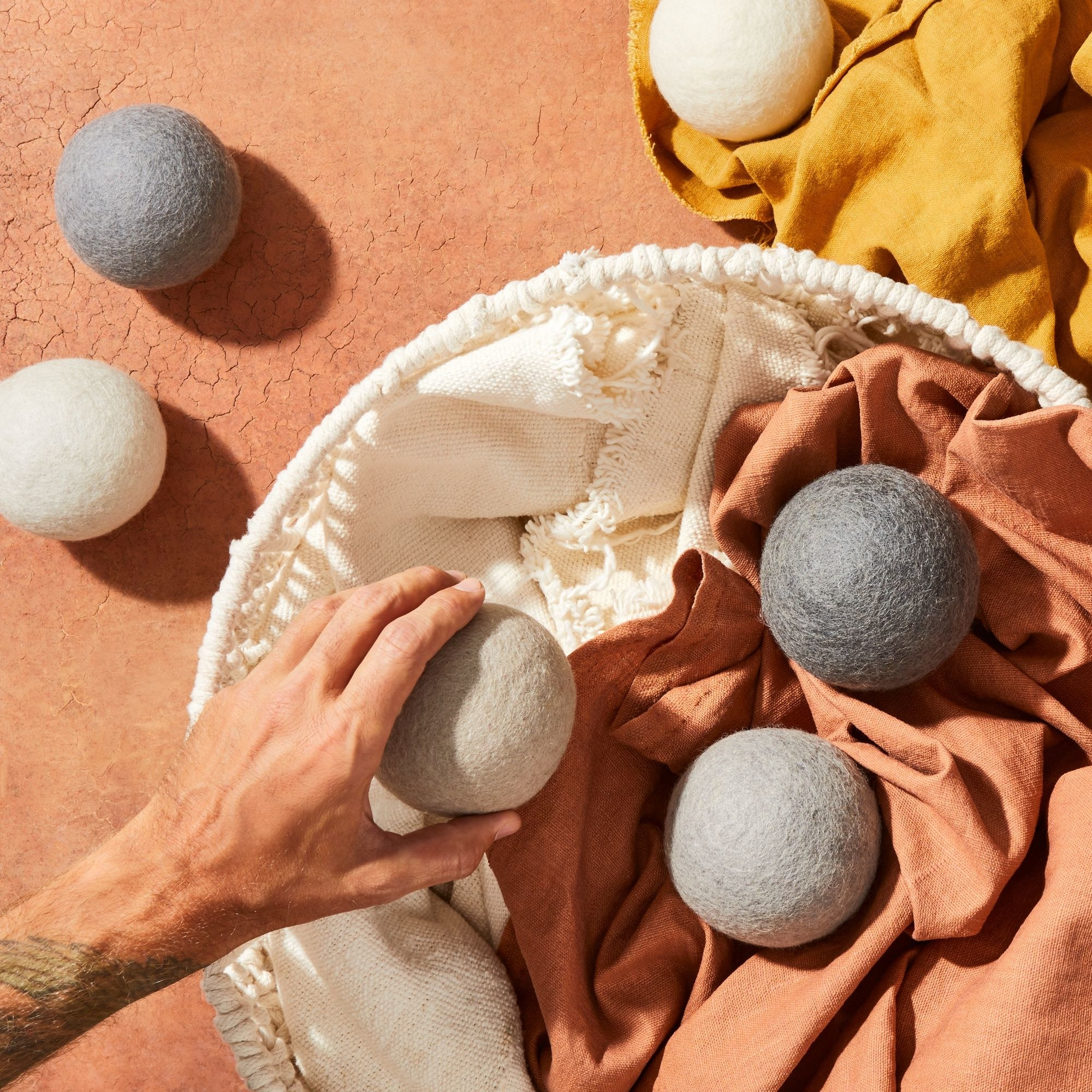A hand reaches for a tennis-ball sized dryer ball