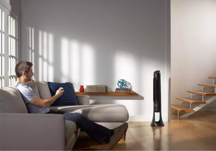 a person aiming a remote at the tower fan in a living room