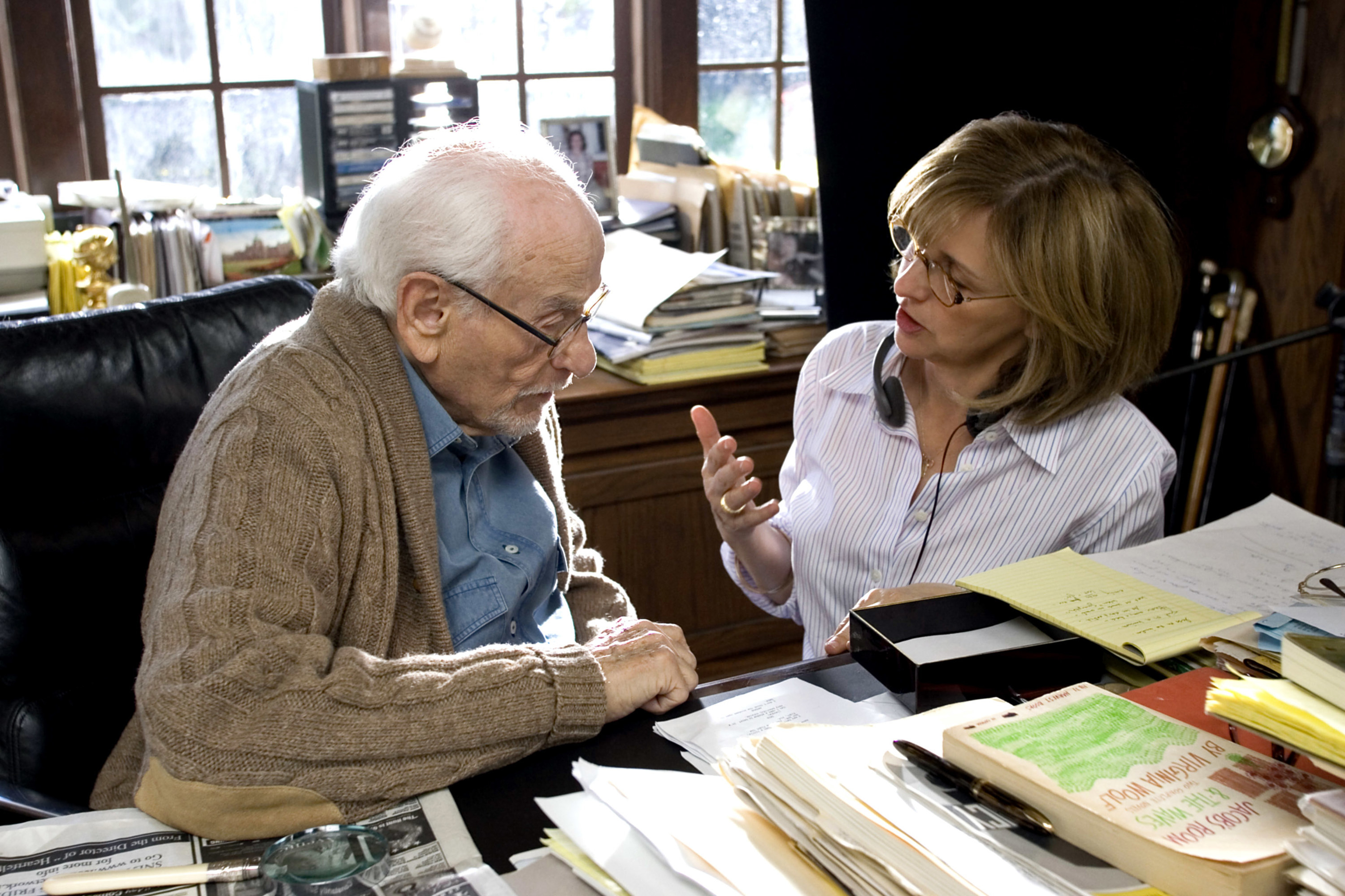 Nancy Meyers talks to Eli Wallach while seated at his desk