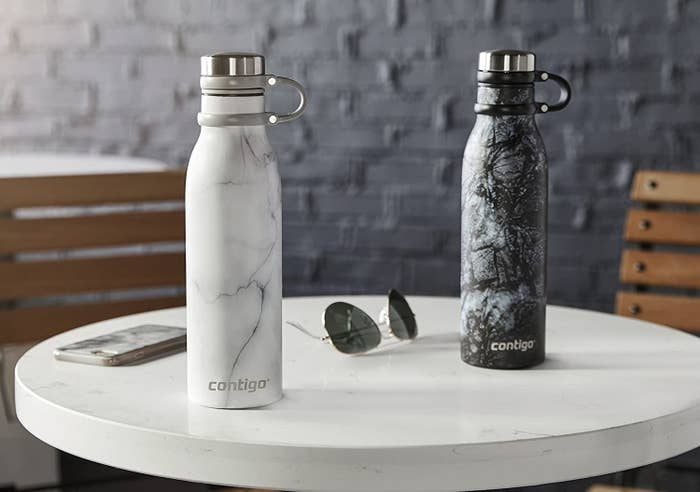 Two water bottles sitting on a low table with a pair of sunglasses and a cell phone next to them
