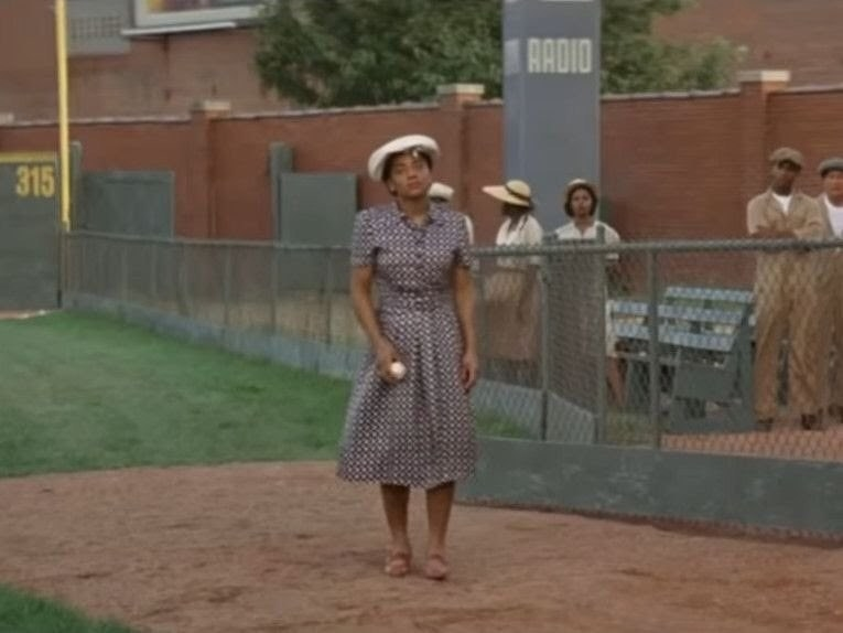 A black woman holding a baseball while walking onto the field