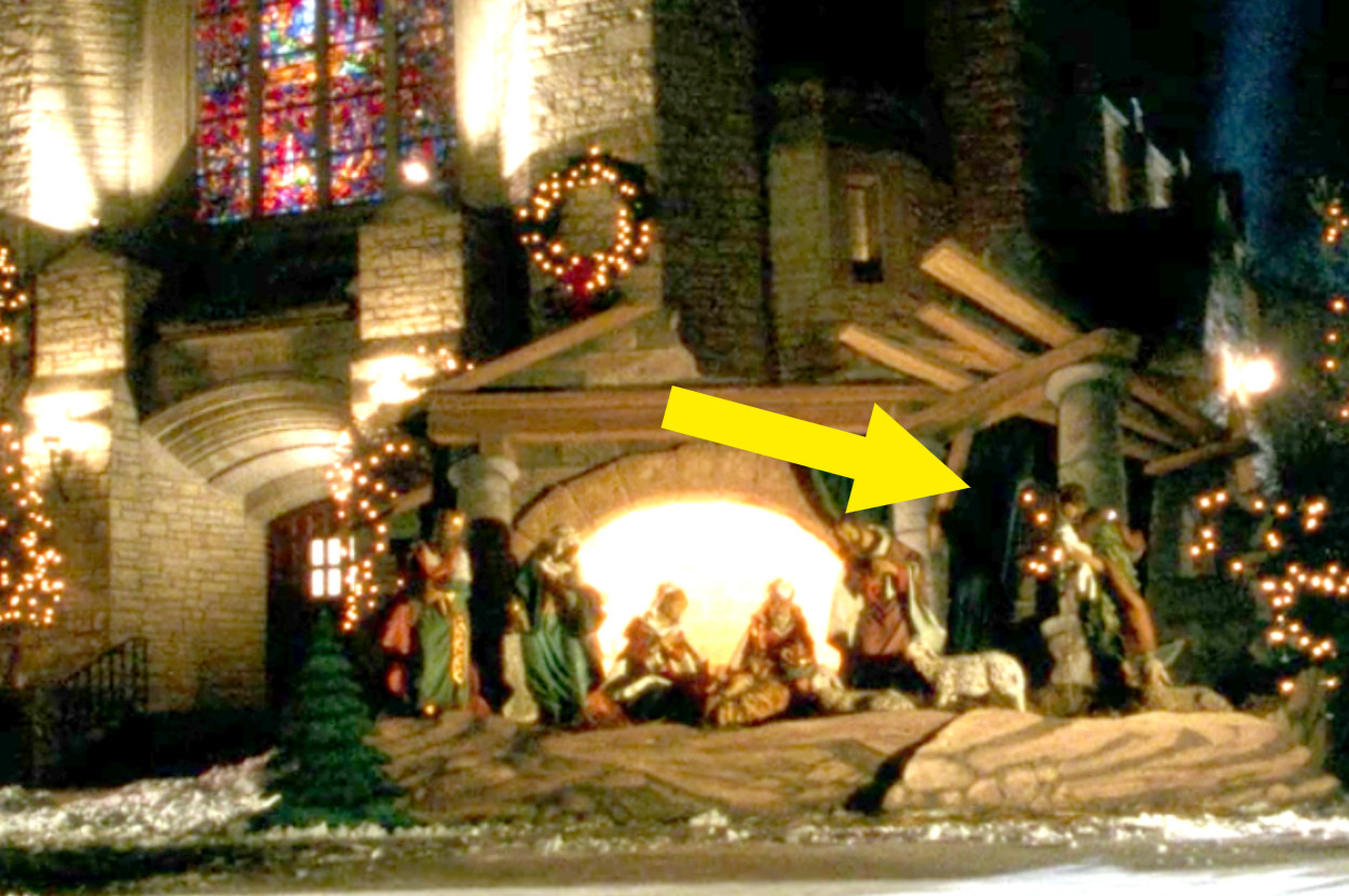 A nativity outside the church where the green curtain is hanging back up again