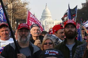 A large group of people wearing Trump paraphernalia with the US Capitol seen in the background