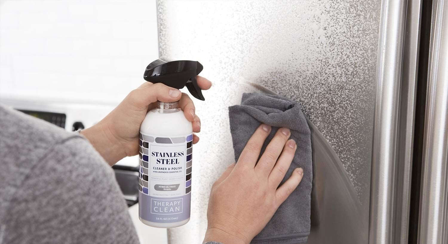 Hands spraying the white cleaner on a fridge, then wiping with a microfiber cloth