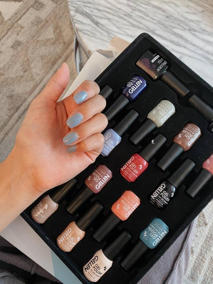 BuzzFeed Editor Kayla Suazo showing the blue gel polish on her nails with the rest of the colors in the set in the background