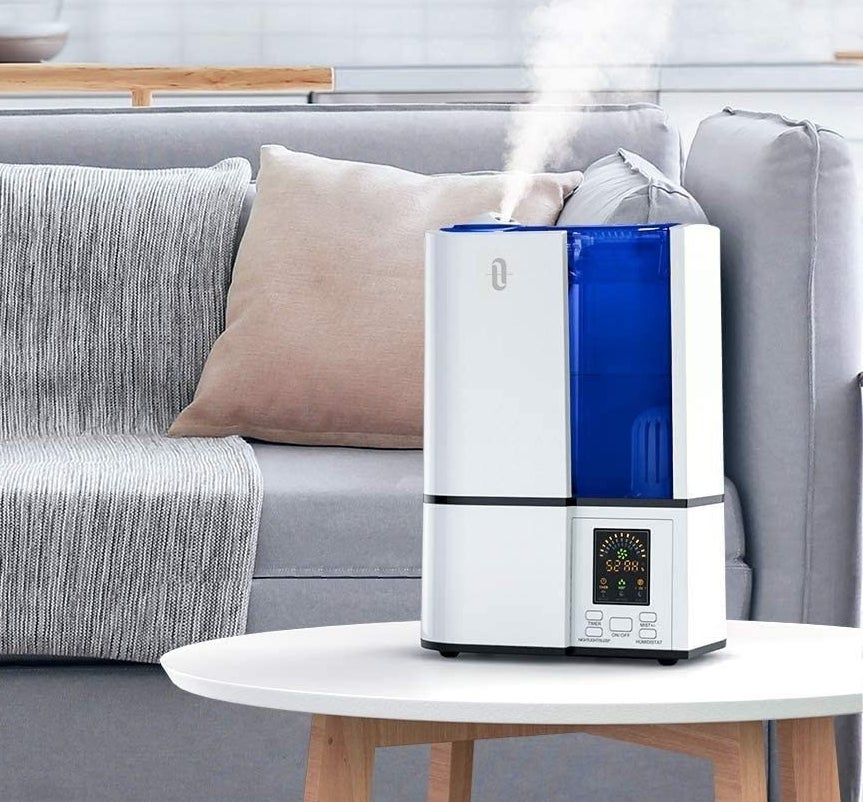 A humidifier on a low table by a couch in someone's living room