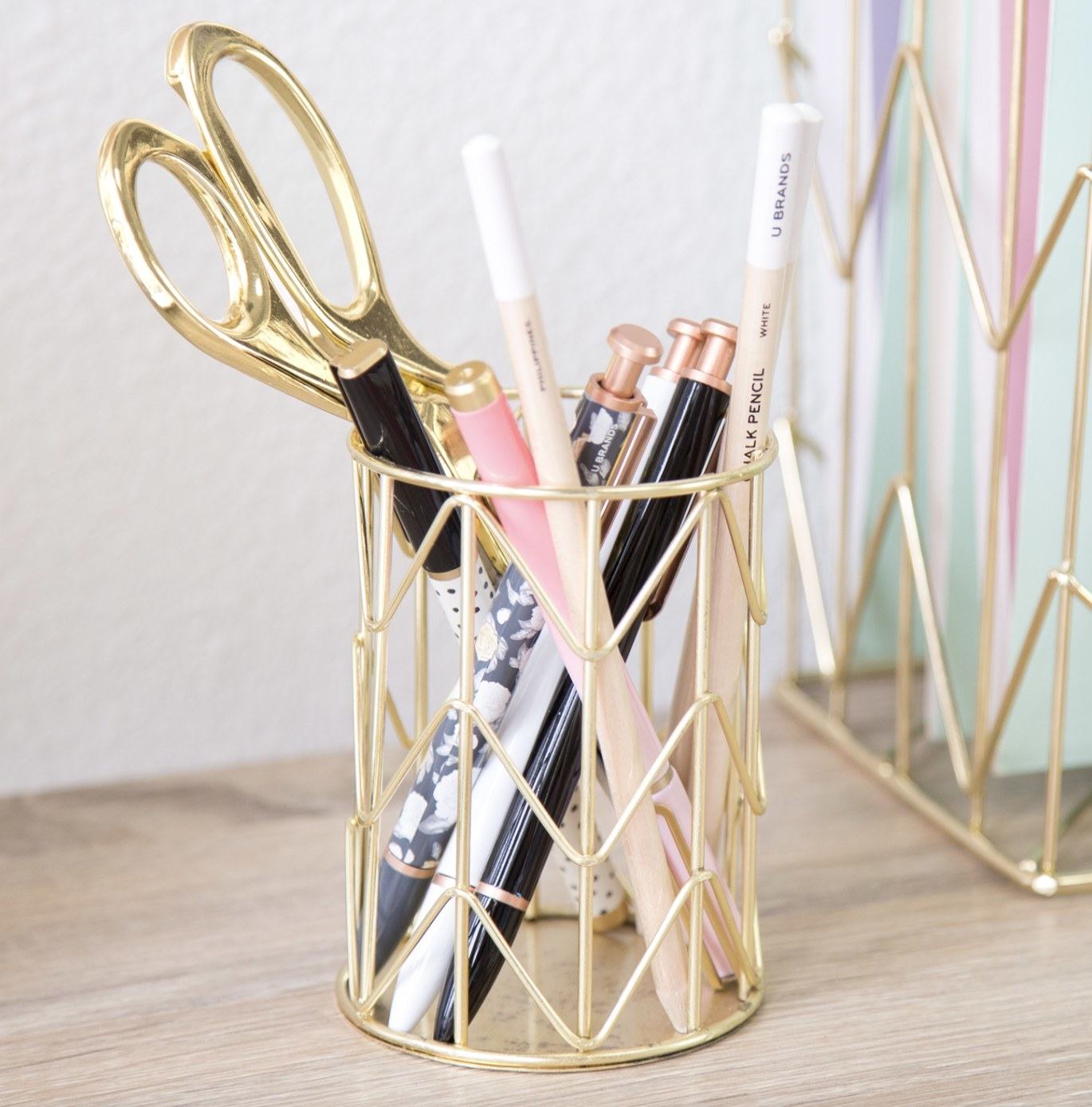 pencil holder with pens, pencils, and scissors inside of it
