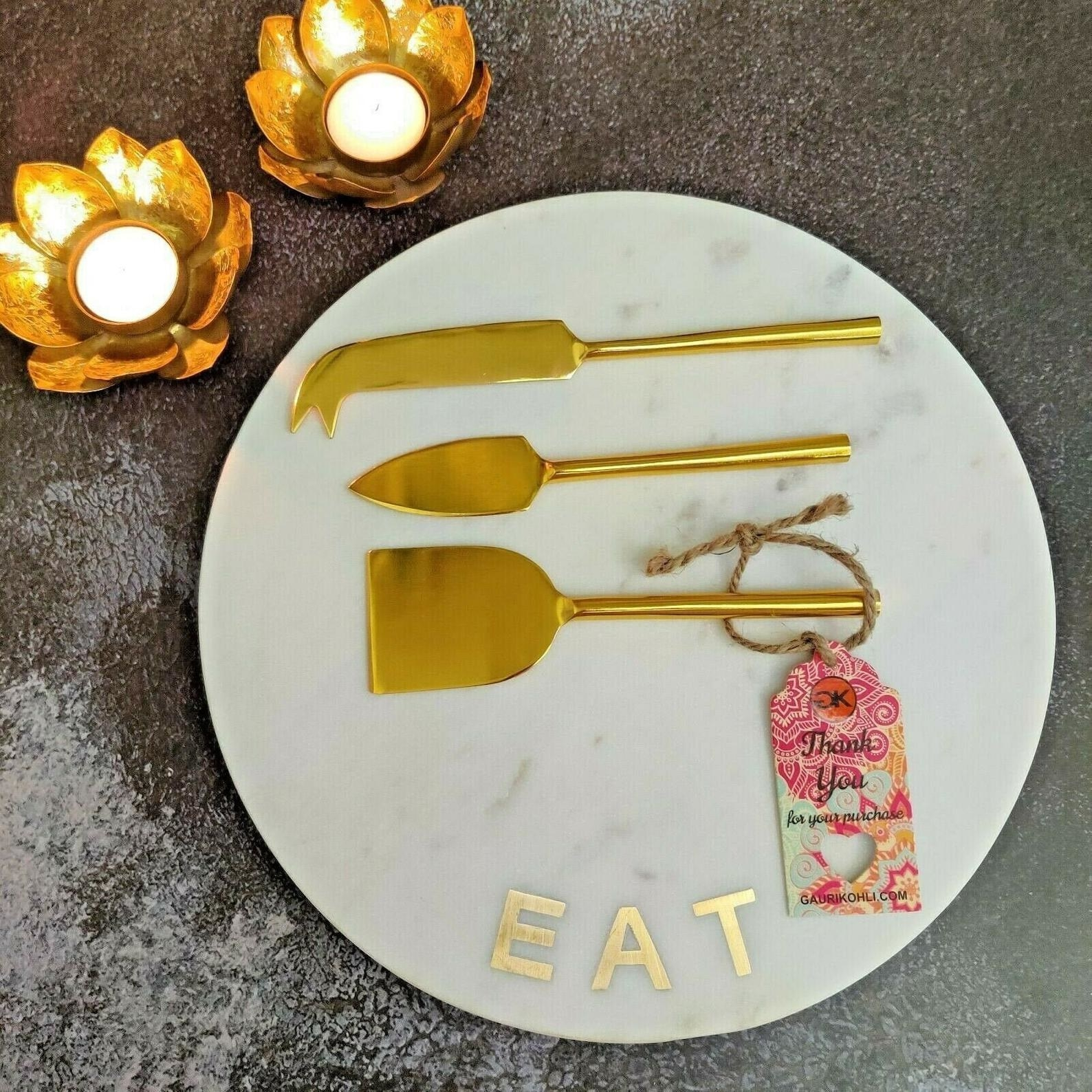 the marble plate that says eat with three gold cheese knives