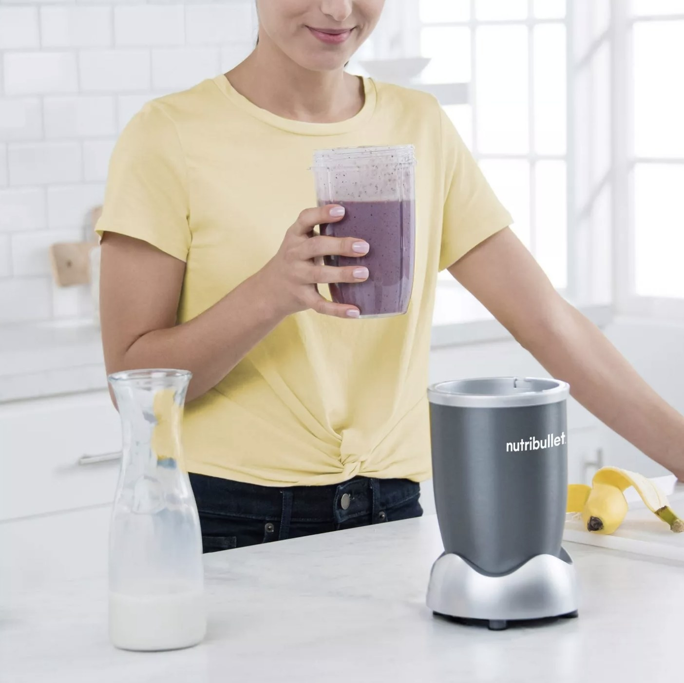Person is drinking a smoothie from the Nutribullet