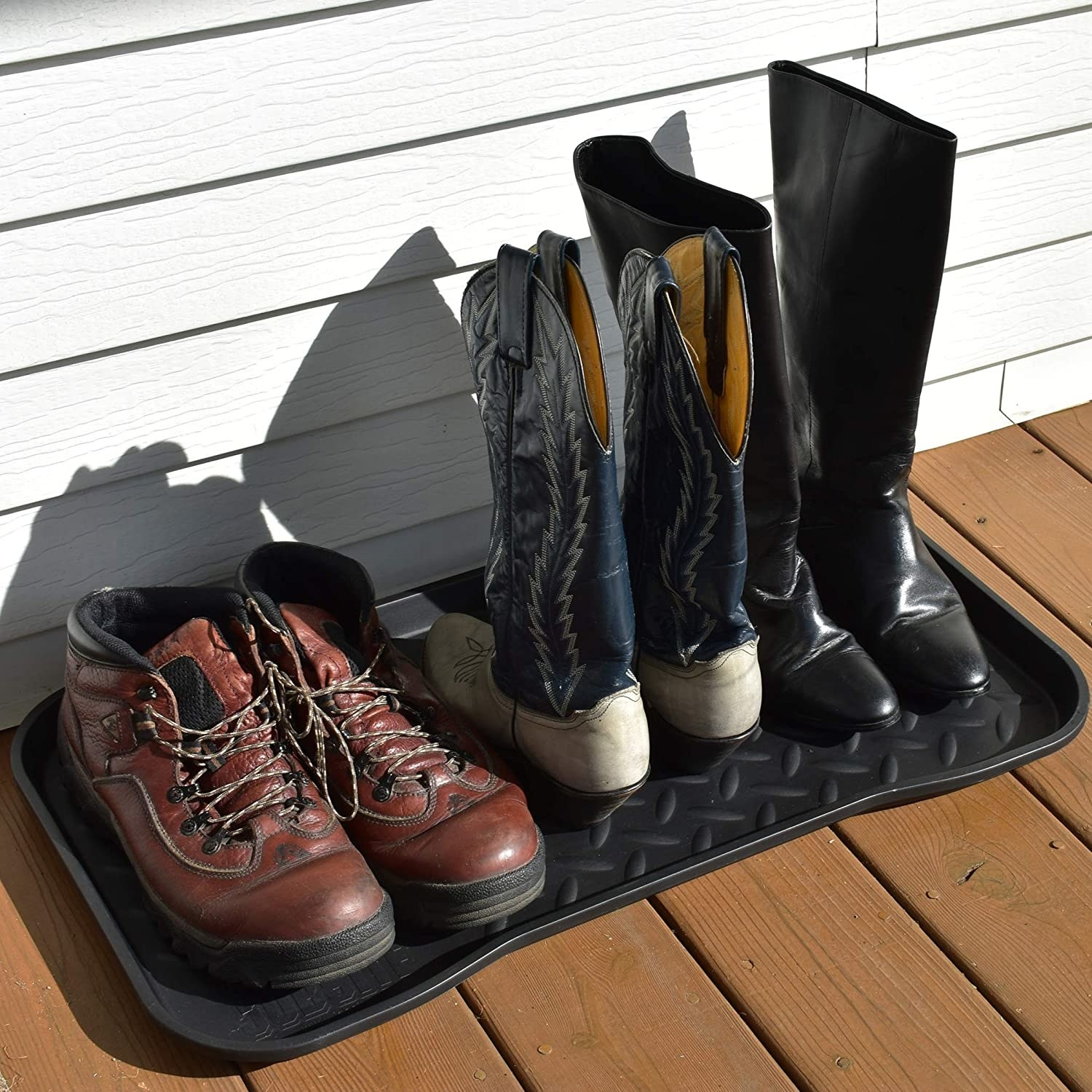 Three pairs of boots on a tray on a porch