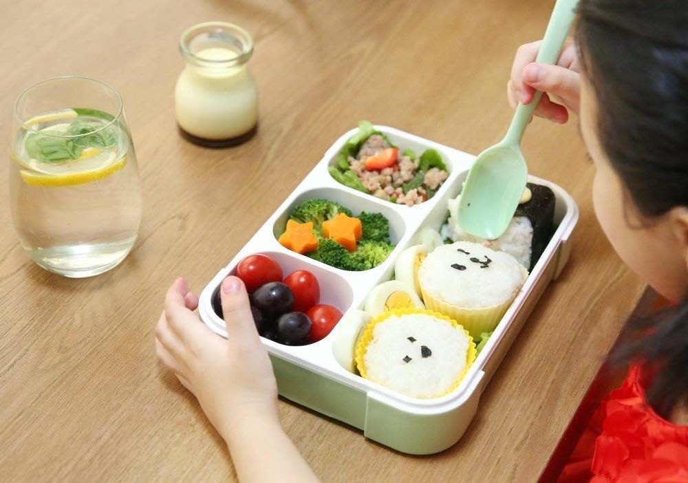 A lunch box with one rectangular compartment and three smaller square compartments.