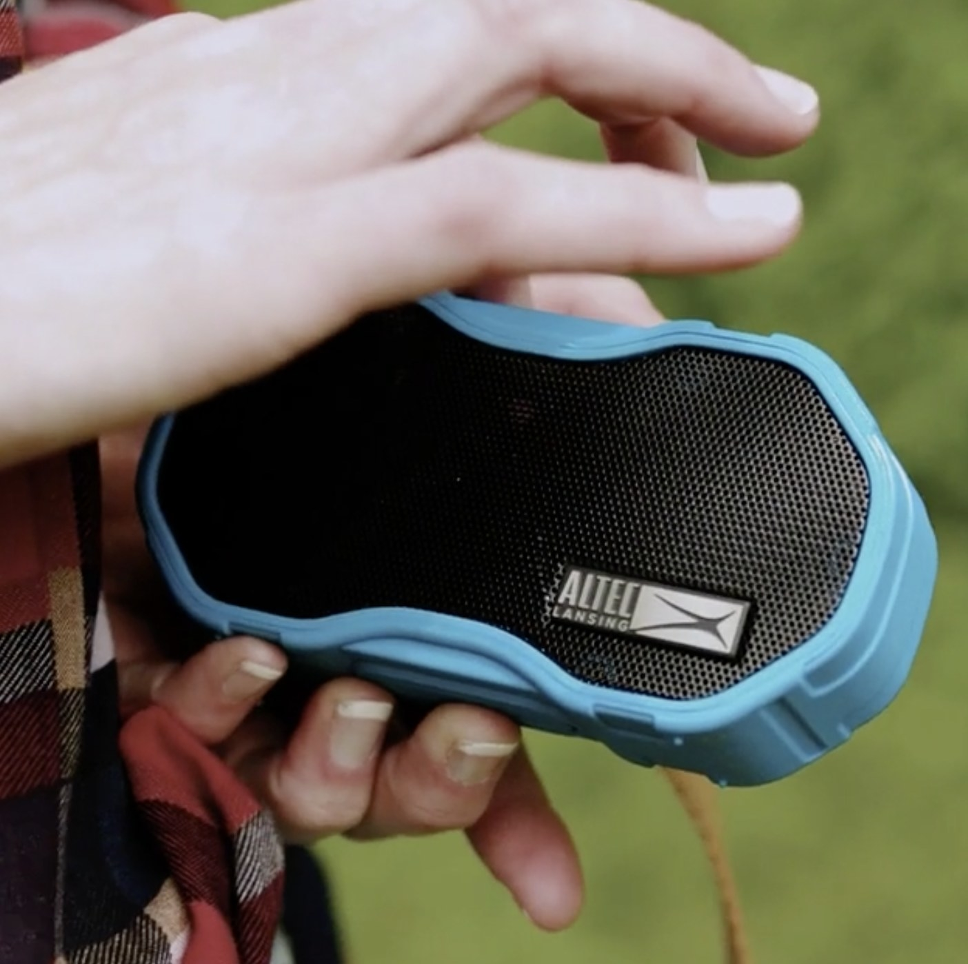 Person is holding a BlueTooth speaker