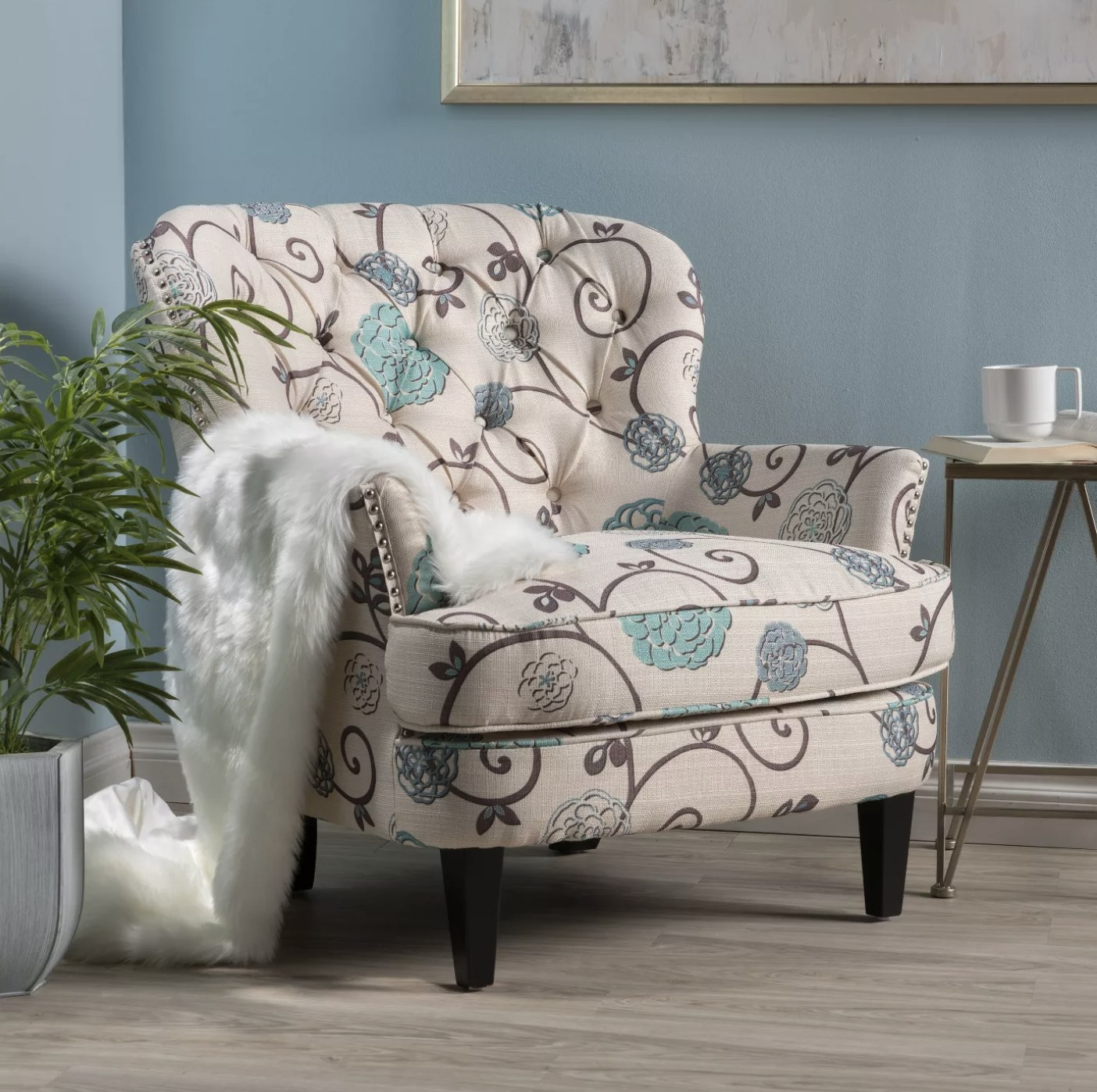 A cream accent chair with a floral pattern