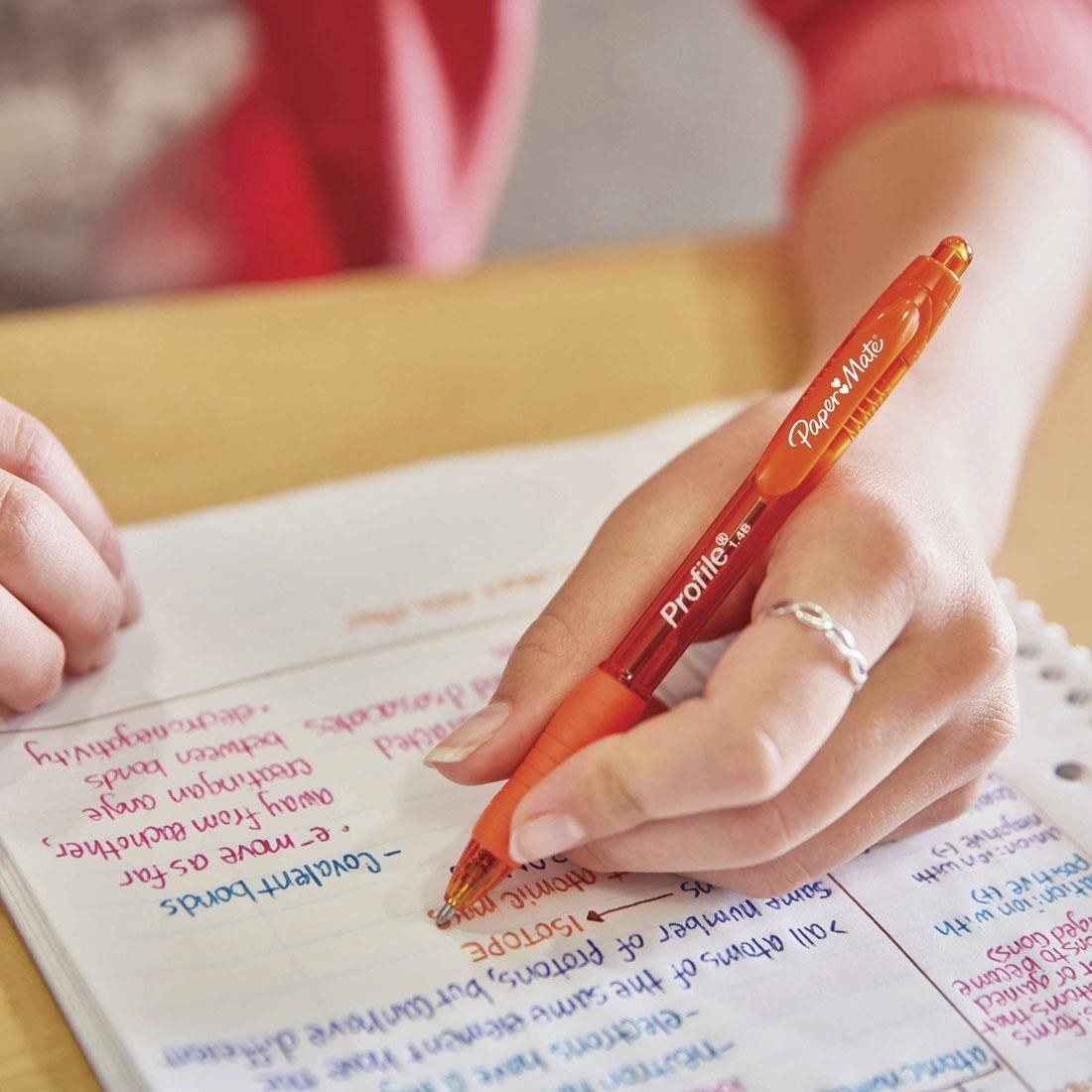 a hand using the orange pen to write notes