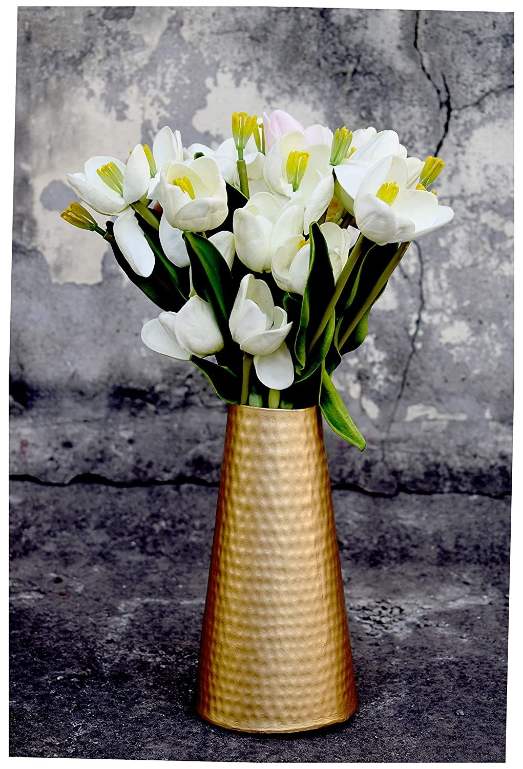 A golden vase with flowers in it