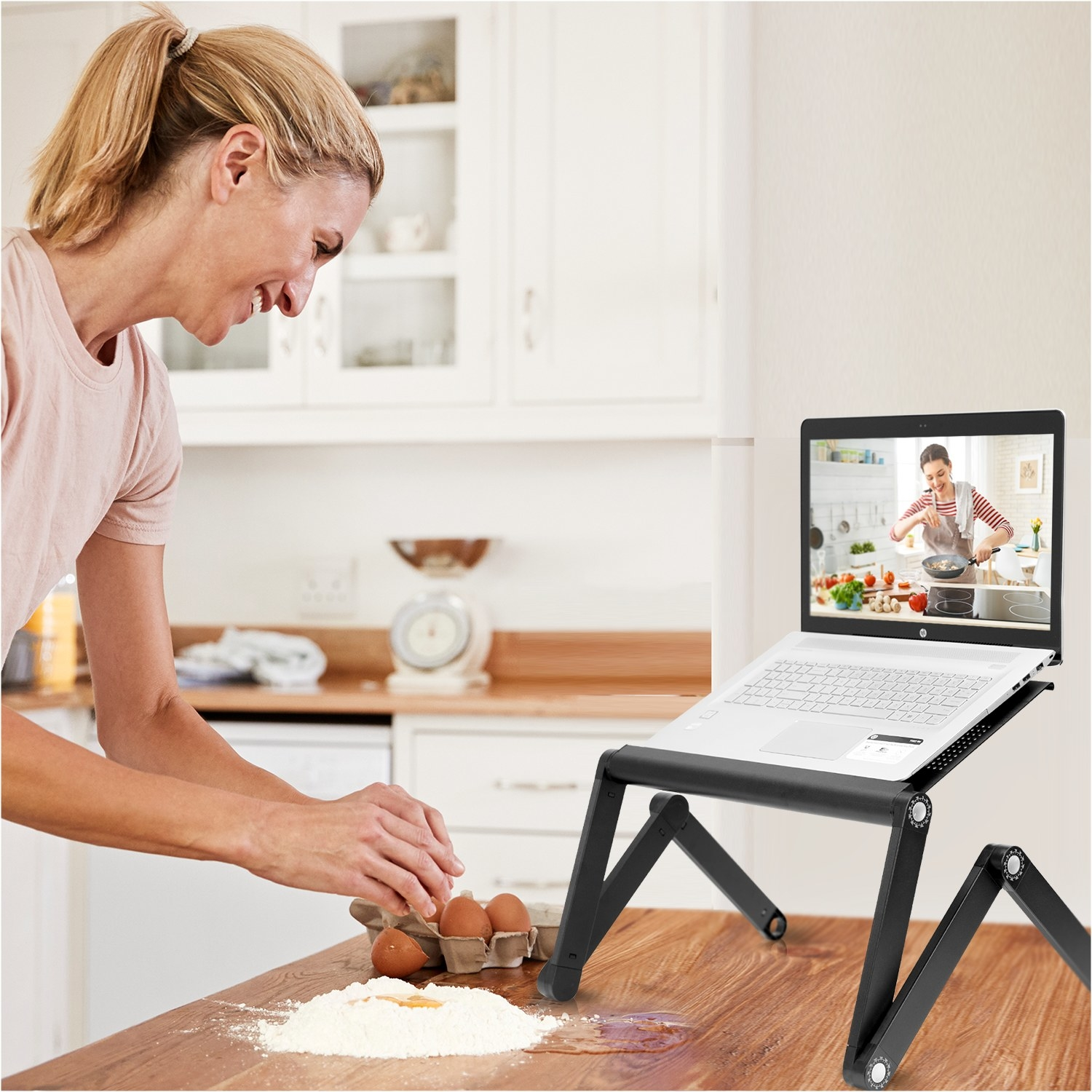 A person using the laptop stand for her computer while taking a baking class