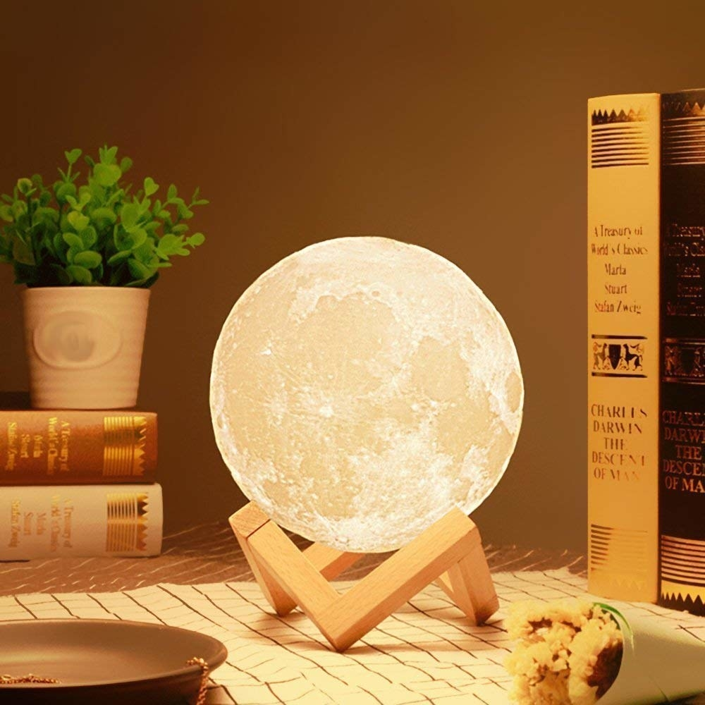 A moon lamp on a stand next to books